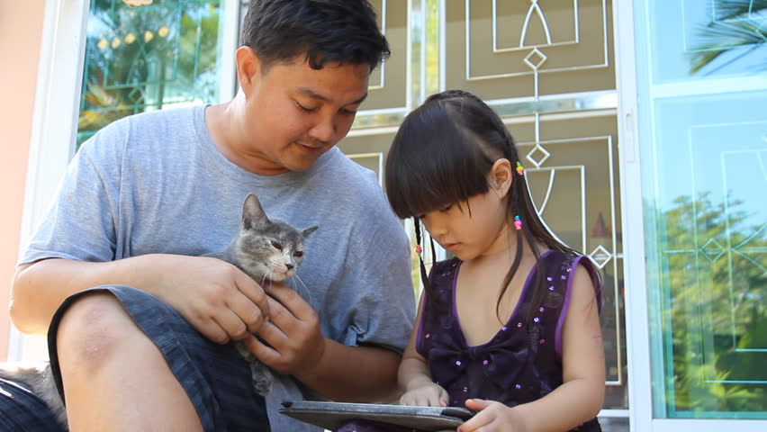 Father,daughter and cat play digital tablet