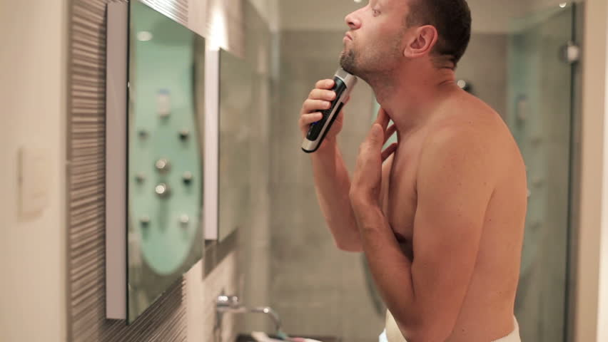 Young man shaving in front of the mirror