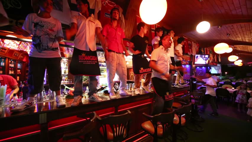 MAHMUTLAR, ALANYA, TURKEY - JUL 10, 2012: Barmen dance on bar at night in restaurant Kogen. There are 40 tables for about 150 people in restaurant.