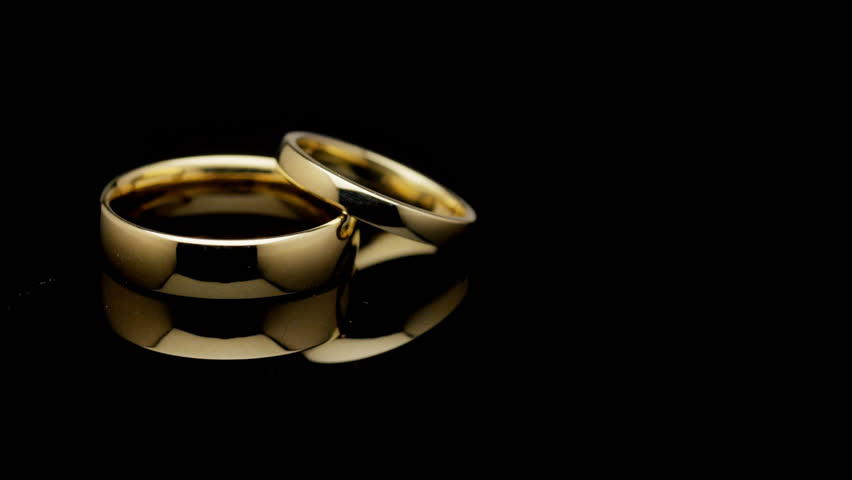 stock video clip of pair of wedding rings turning on black