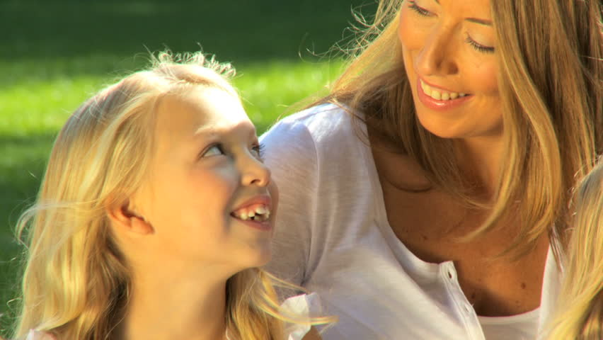 Attractive mother tenderly talking to her daughter while outdoors on a summers day | Shutterstock HD Video #540742