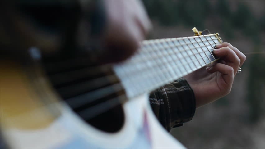 Close Up Of Cute Teen Outdoors In A Hoody Softly Strumming Her Guitar
