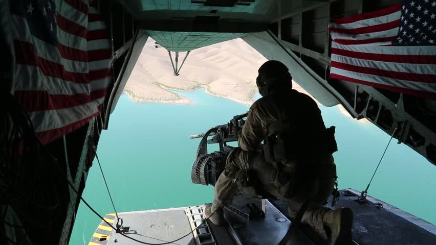 Tailgunner Sits in Open Doorway of Helicopter over Afghanistan while U.S. Flags Wave in the Breeze