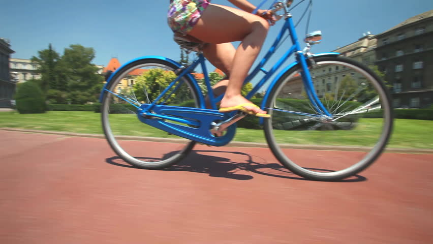 View of legs of beautiful young woman cycling on old vintage bike in city park area