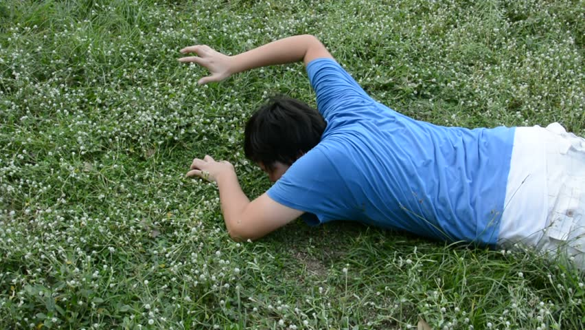 An Asian male Thai guy is struggling for life crawling with hunger and thirst in a vast green grass field but couldn't make it at last. Death action concept in HD.