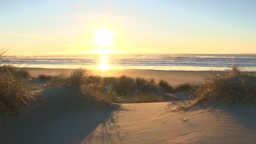 Coastline at sunset, real time at pacific ocean on breezy evening by sand dunes.