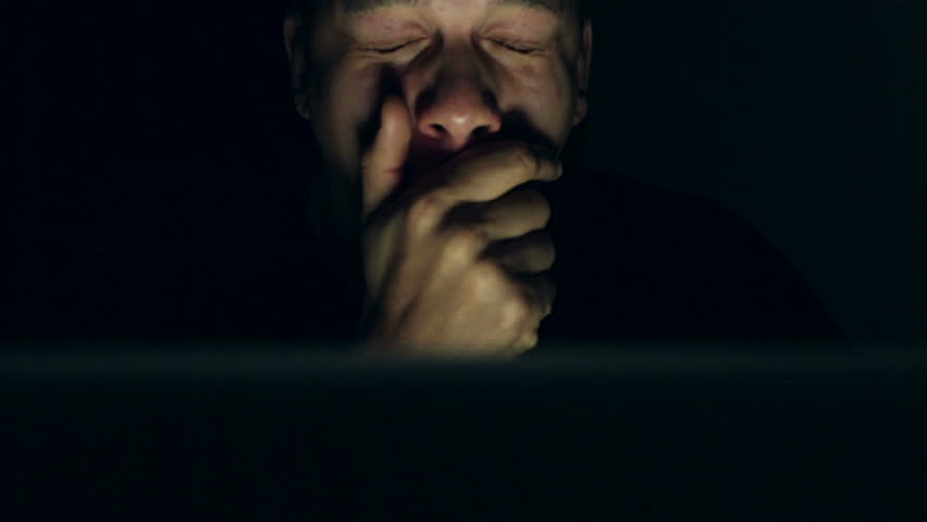 Tracking shot of a young mixed race man on his laptop at night looking very tired but pressing on with his work | Shutterstock HD Video #5483723