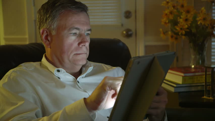 Relaxing at home using his tablet pc a mature handsome man smiles contentedly. | Shutterstock HD Video #5483882