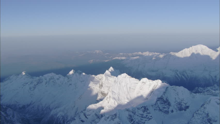 Peaks Snow Polar Rocky Mountains. A spanning look down the steep rugged nose of a snow covered mountain ridge. footage shows polar rocky mountain range from highest altitude of the mountain peaks.