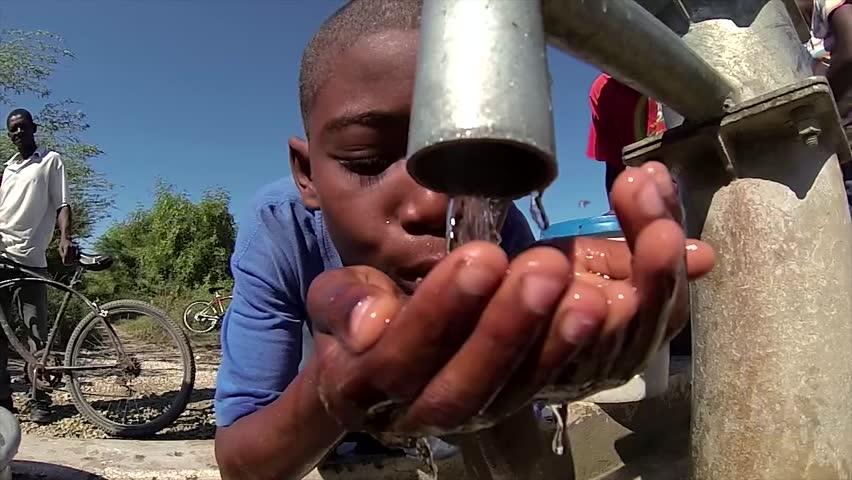 PORT AU PRINCE, HAITI - DECEMBER 17, 2013: Unidentified boy gets drink of fresh water at well in Port au Prince, Haiti.