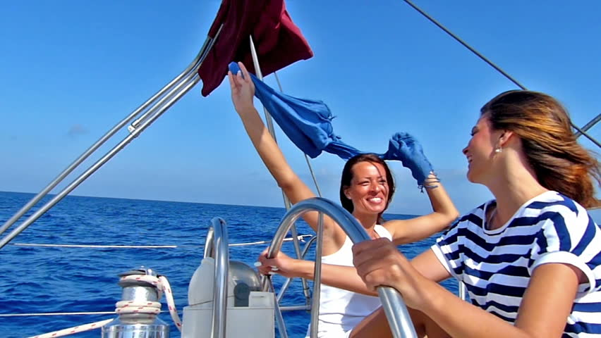 Young female skipper and her friend enjoying on the yacht.Slow motion, high speed camera