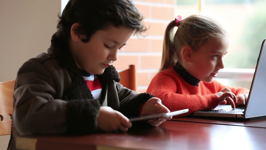smart children studying, using digital tablet and laptop at classroom