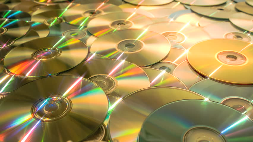 Sliding dolly shot forward over a sea of discs, DVDs and CDs