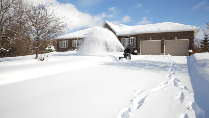 Man using a gas powered walk behind snowblower to clear his driveway of snow at home after a winter snow storm | Shutterstock HD Video #5563292