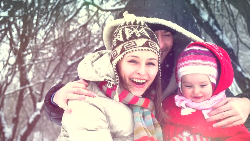 Beautiful Winter Family having fun outdoors. Happy laughing father, mother with their little baby girl playing in Winter park. Mom and Dad with a child. Snow. Slow motion 240fps. Slowmo 1080p