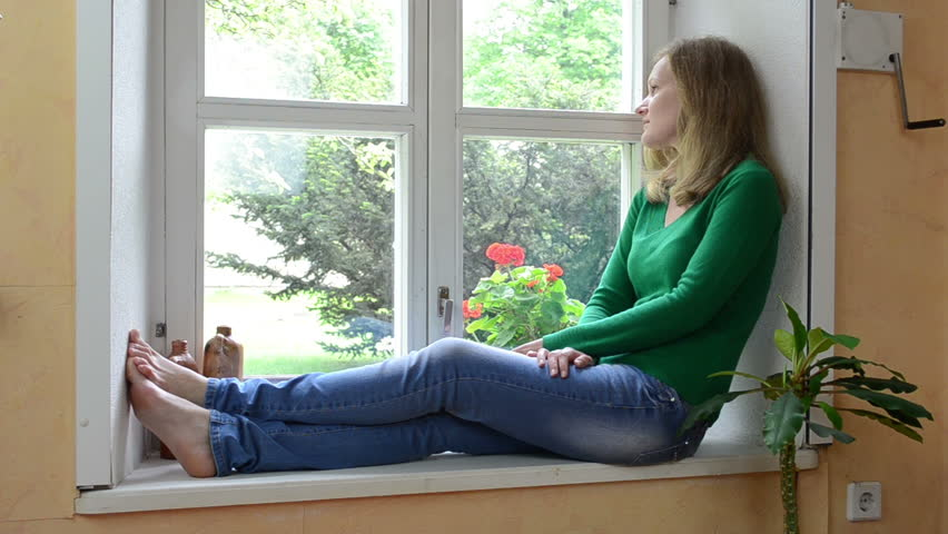 wife woman sit on sill and watch through window waiting for husband. - HD  stock