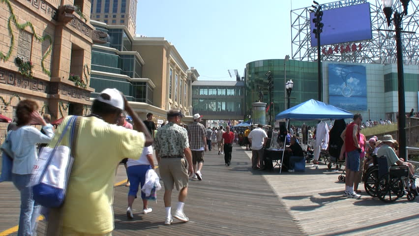 People walking on the boardwalk at Atlantic City with the screen of the Airshow