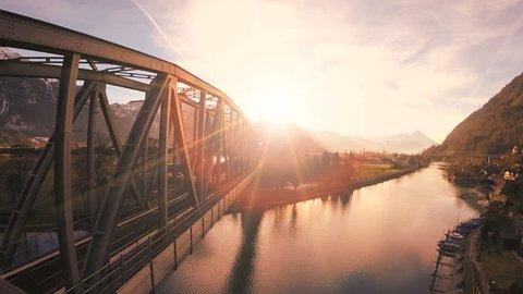 epic flying view. bridge road. street train traffic transportation. lake river pond. panorama landscape. sunset sky