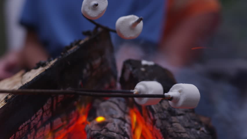 Family roasting marshmallows by outdoor fire. Shot on RED EPIC for high quality 4K, UHD, Ultra HD resolution.