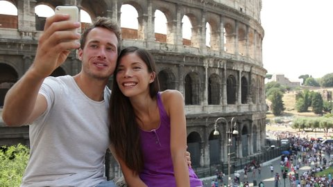 Tourist couple on travel taking selfie self-portrait pictures by Coliseum in Rome. Happy young romantic couple traveling in Italy, Europe taking photo with smartphone camera in front of Colosseum.
