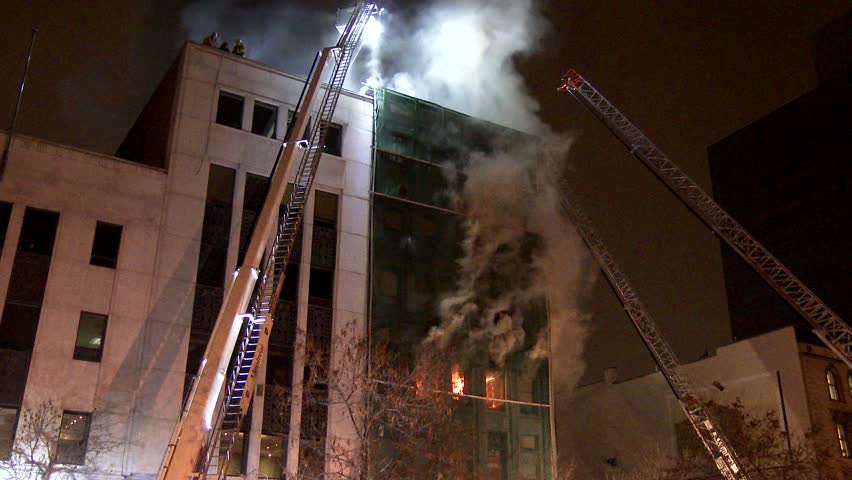 MONTREAL, QC - 1/2014 - 4K 60fps - Steady shot of fire & ladders. Tripod mounted shot of building on fire with firemen on the roof with flames and multiple ladders and fire trucks.