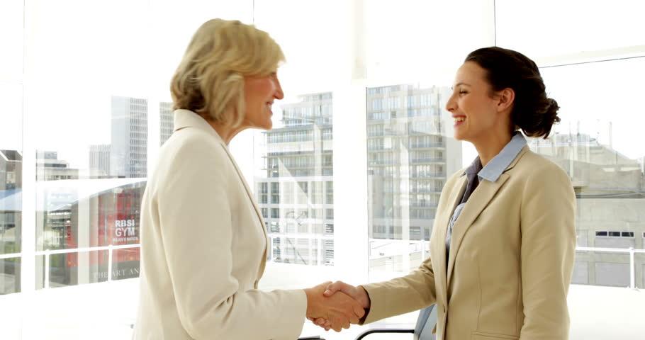 Smiling businesswomen shaking hands in the office   Shutterstock HD Video #5658782