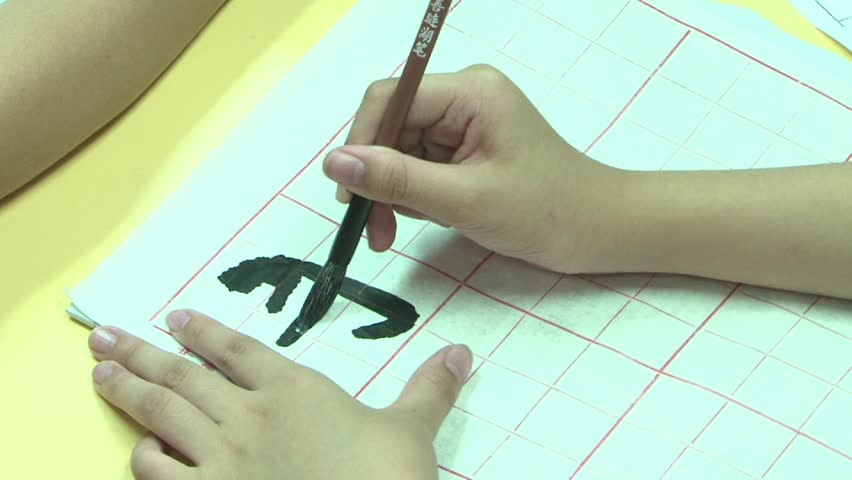 girl doing Chinese calligraphy in a notebook striped
