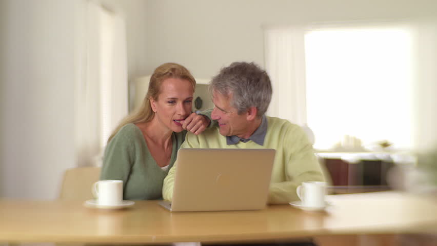 Mature couple using laptop and drinking coffee | Shutterstock HD Video #5684552