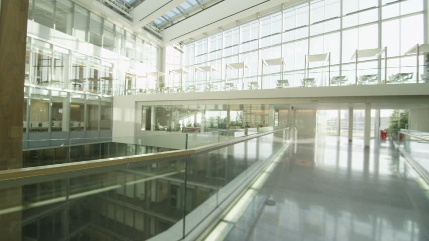 Interior view of a large contemporary office building with glass partitions and large central atrium. No people.