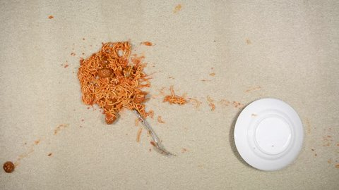 A plate of spaghetti is accidentally knocked to the floor, leaving an ugly mess.