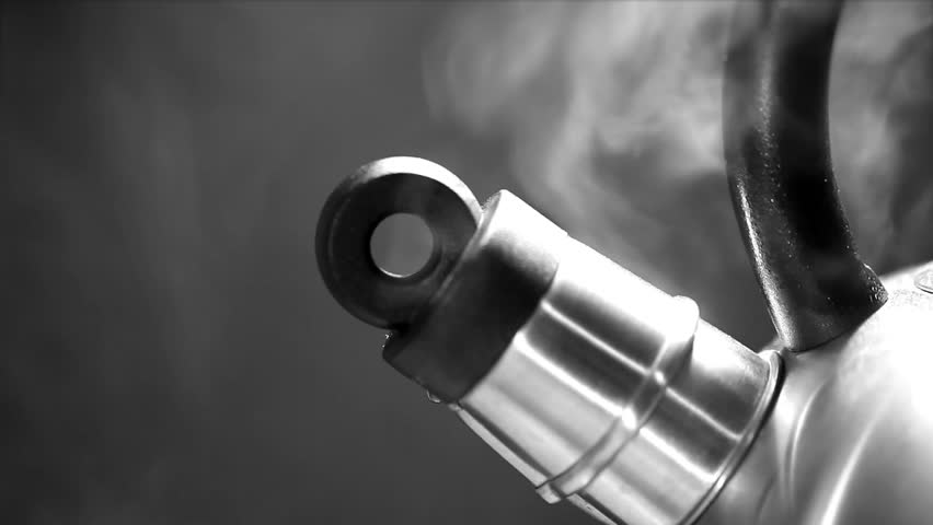 Close up of a part of teapot spraying steam in a black background.