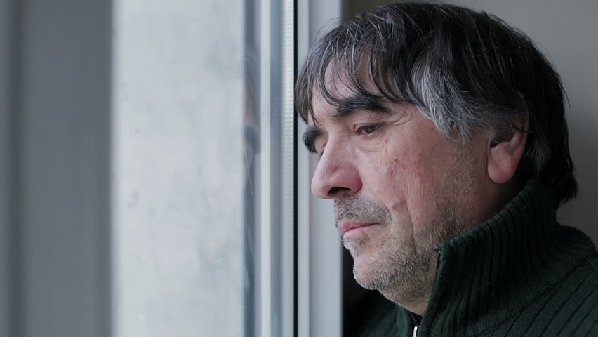 sad and pensive mature man at the window