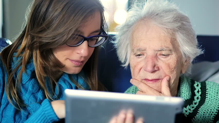 Young woman teaches her grandmother work with computer - senior lifestyle