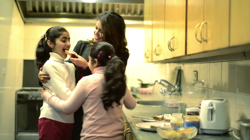 Shot of a mother with her daughters having breakfast in kitchen