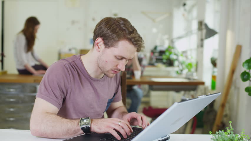 Young male student concentrating as he works within a shared study space | Shutterstock HD Video #5763200