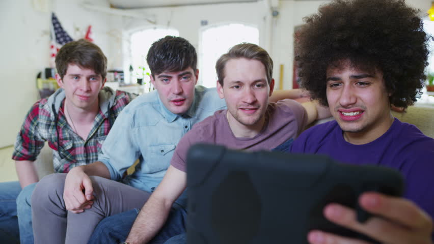 Happy and casual group of young male friends, hanging out at home and reacting with disgust at what they see on the screen of a digital tablet. In slow motion.