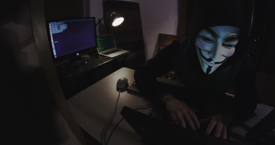 New York Ny Usa Circa 2017 A Hacker Activist Sits At Their Laptop Computer In Grungy Apartment They Are Wearing Guy Fawkes Mask Which Has Become