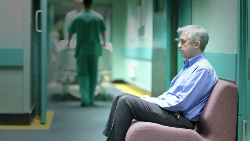 Time lapse. A worried man sits alone with his thoughts in a hospital waiting area as staff and other visitors rush around him.