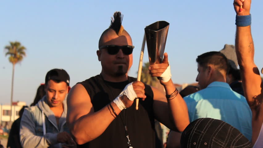 VENICE BEACH, CALIFORNIA, FEBRUARY 2014: A man with a crazy Mohawk hairdo plays his cowbell at the Venice Beach Drum Circle in Los Angeles.