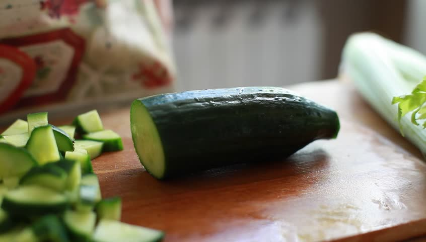 Female hands chopping cucumber (HD, high definition 1080p, 1920x1080, hidef) beautiful shot with soft focus. Healthy food concept. Dolly shot