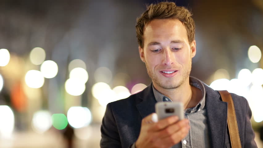 Man sms texting using app on smart phone at night in city. Handsome young business man using smartphone smiling happy wearing suit jacket outdoors. Urban male professional in his 20s. | Shutterstock HD Video #5815802