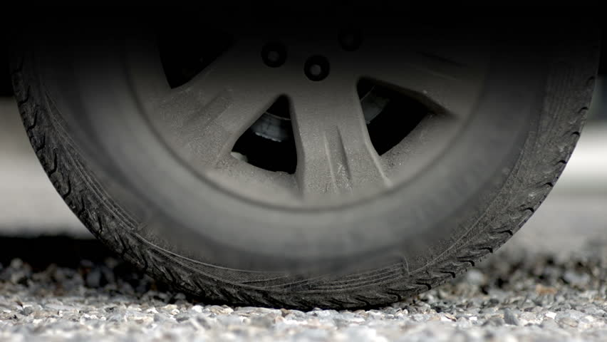 Close up of a vehicle wheel turning and trying to gain traction against the gravel road surface. As the wheel spins and moves off it sends fragments of grit flying. In slow motion.