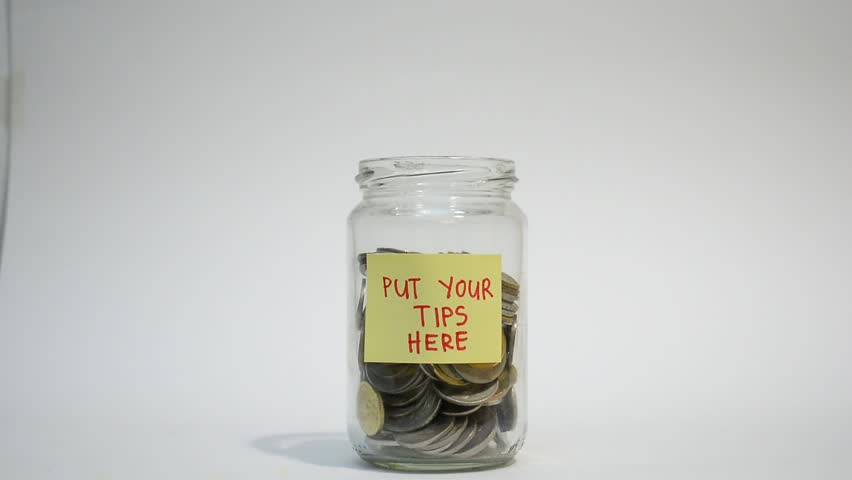 Hand putting money in jar with 'Please put your tips here ' label