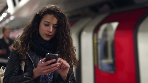 Attractive young woman using her mobile cell phone as a subway underground train arrives