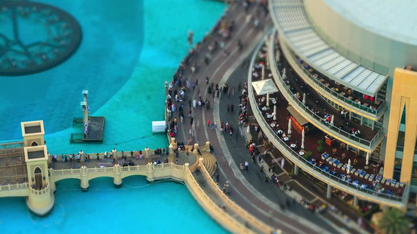 Dubai Mall timelapse near fountain with bridge. People walking down the street near the mall