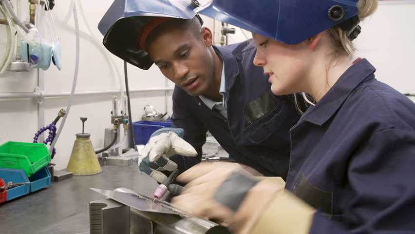 Engineer explaining to female apprentice how to use TIG welding machine before they both lower protective face masks.Shot on Sony FS700 in PAL format at a frame rate of 25fps