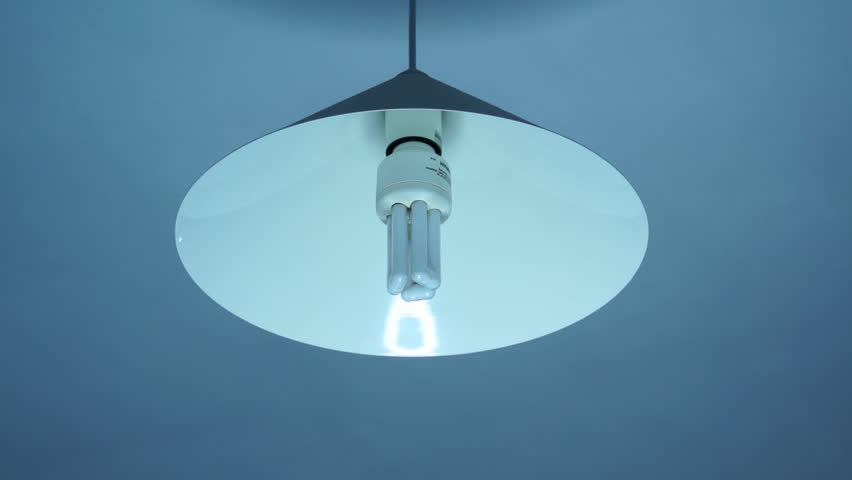 Compact Fluorescent Light Bulb lights on and off. Turning a compact fluorescent light bulb on and off. Energy saver light.