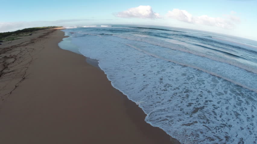 2.7K Ultra HD Aerial Smooth Gliding Pan Forward of Perfect Secret Beach in Kauai Hawaii with Sets of Waves Breaking Along the Sand