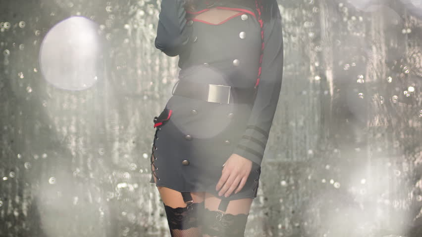sexy beautiful woman dancing in military fetish style fancy dress outfit in  disco setting