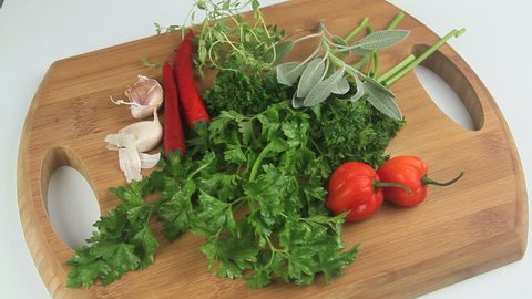 Time lapse build up of fresh herbs appearing on a wooden cutting board.